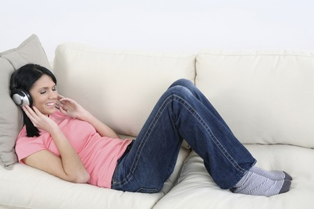 Woman lying down on the couch, smiling while listening to MP3 player Stock Photo - 4099875