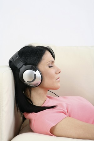 english ethnicity: Woman lying down on the couch, listening to MP3 player with her eyes closed Stock Photo
