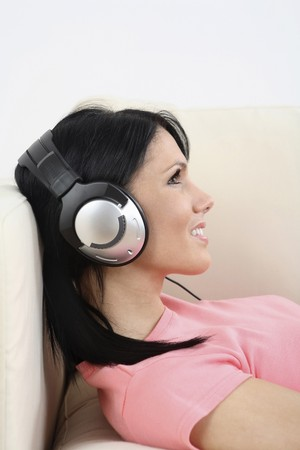 english ethnicity: Woman lying down on the couch, smiling while listening to MP3 player