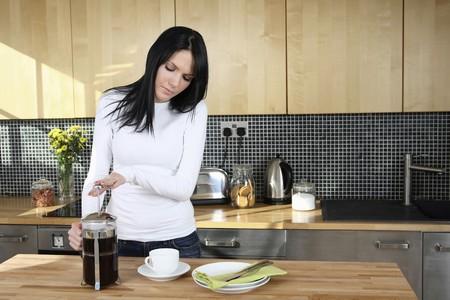 女性が台所でコーヒーを準備します。