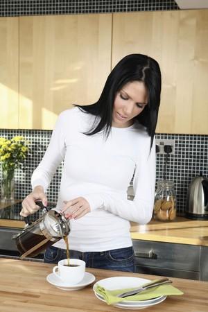 La mujer vierte el café en la taza Foto de archivo - 4099826