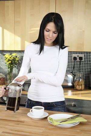 english ethnicity: Woman preparing coffee in the kitchen Stock Photo