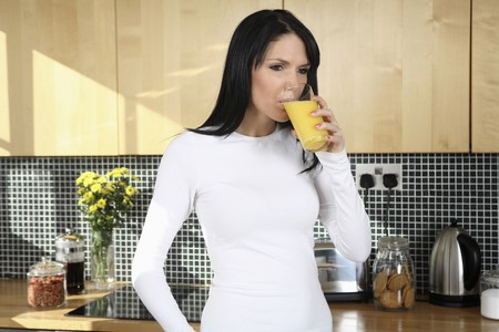 english ethnicity: Woman drinking a glass of orange juice