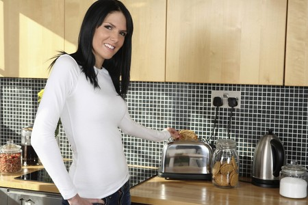 english ethnicity: Woman taking toast out of toaster