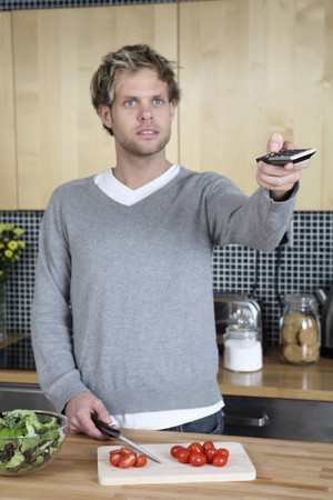 Man changing channel with remote control while cutting vegetables in the kitchen photo