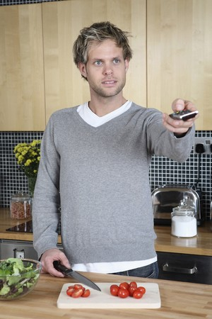 changing channel: Man changing channel with remote control while cutting vegetables in the kitchen Stock Photo