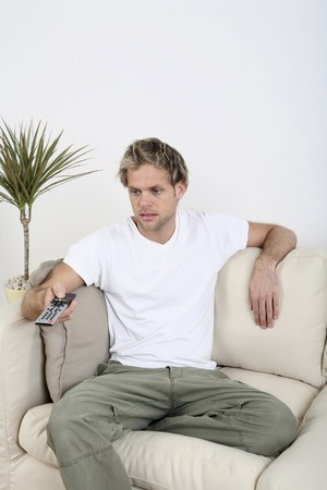 Man changing channels with remote control Stock Photo - 4099796
