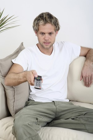 Man changing channels with remote control photo