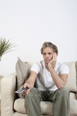 Man changing channels with remote control Stock Photo - 4099791