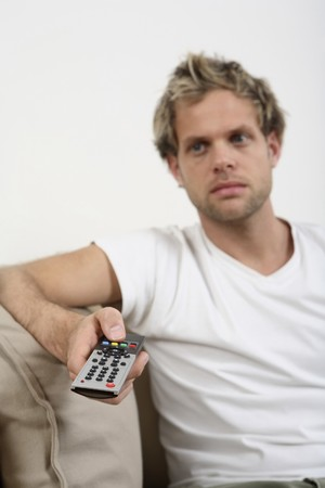 Man changing channels with remote control Stock Photo - 4099067
