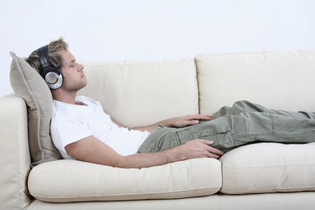 resting: Man with headphones relaxing on the couch, listening to music