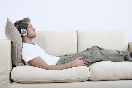 Hombre con auriculares de relax en el sofá, escuchar música