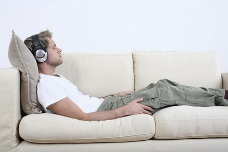 lying on couch: Man with headphones relaxing on the couch, listening to music