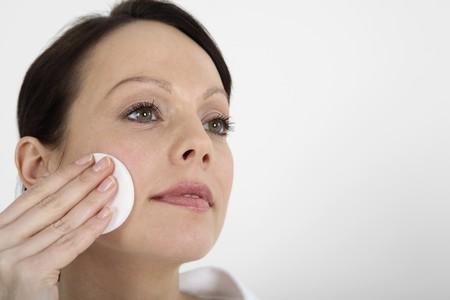 pulizia viso: Donna di pulizia del viso utilizzando il suo viso spugna Archivio Fotografico
