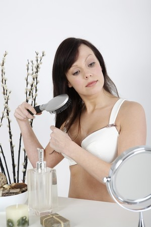 Woman combing her hair using a hair brush
