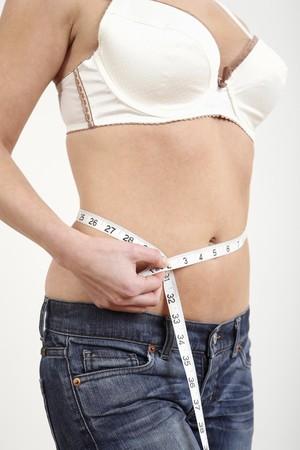 허리의 잘룩 한 선: Woman measuring her waistline 스톡 사진