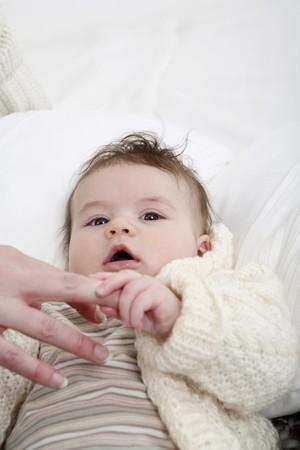 Baby holding womans finger Zdjęcie Seryjne
