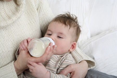 Woman feeding baby with milk