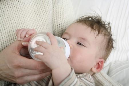 Woman feeding baby with milk photo