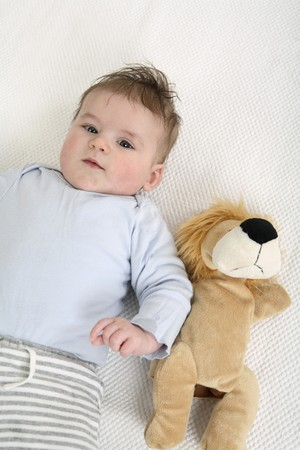 soft toy: Baby lying down with his soft toy beside him Stock Photo