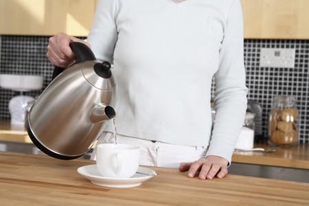warm water: Woman gieten van heet water in haar kopje koffie Stockfoto