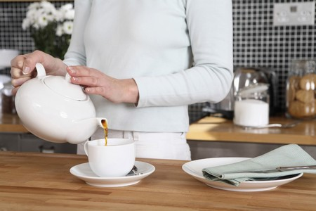 stand teapot: Woman pouring coffee into cup