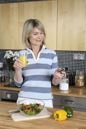 Woman with a glass of orange juice text messaging on the phone photo