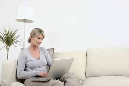 ラップトップを使用してソファの上に座っている女性