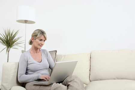 english ethnicity: Woman sitting on the couch, using laptop