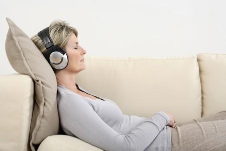 Mujer tendida en el sofá, escuchar música con los ojos cerrados
