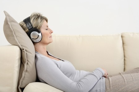 Woman lying on the couch, listening to music with her eyes closed