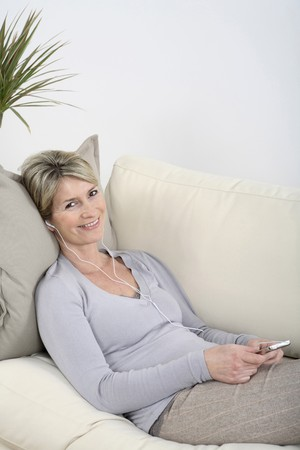 Woman lying on the couch, smiling while listening to music photo