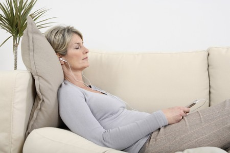 Woman lying on the couch, listening to music with her eyes closed photo