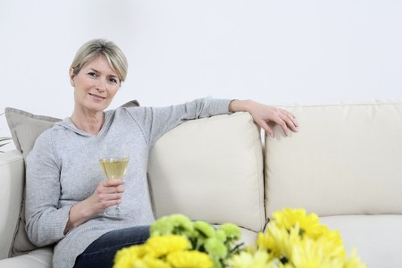 Woman relaxing on the couch, holding a glass of champagne Stock Photo - 4111022