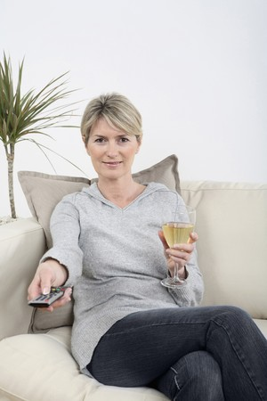 Woman holding a glass of wine while changing channel