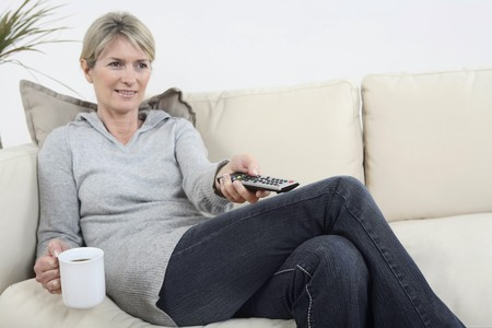 Woman holding a cup of coffee while changing channel