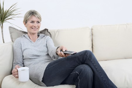 Woman holding a cup of coffee while changing channel photo
