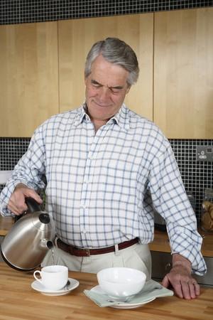 warm water: Senior man gieten warm water in de beker