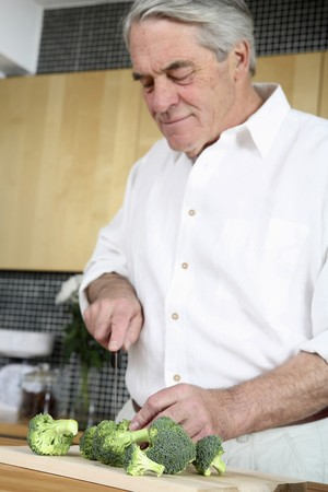 Senior man cutting vegetables in the kitchen Stock Photo - 4110365