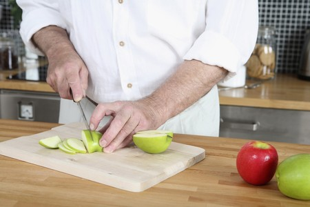 Senior man cutting apples in the kitchen photo