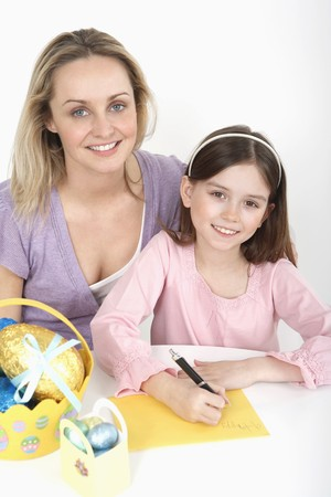 Girl writing an Easter card with woman beside her photo