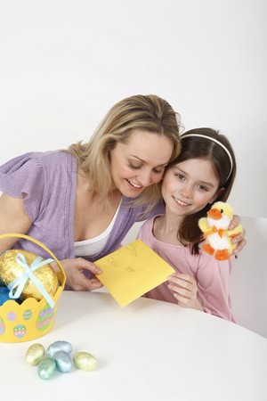 Girl giving Easter card to woman