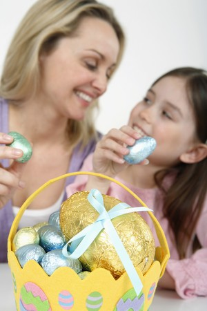 Woman and girl holding Easter egg with Easter basket in the foreground Stock Photo - 4110688