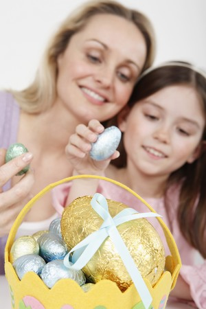 Woman and girl holding Easter egg with Easter basket in the foreground photo