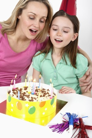 blow out: Woman and girl about to blow out candles together