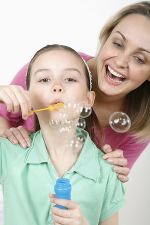 Girl blowing bubbles with woman watching her photo