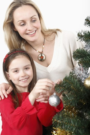 Woman and girl decorating Christmas tree together photo