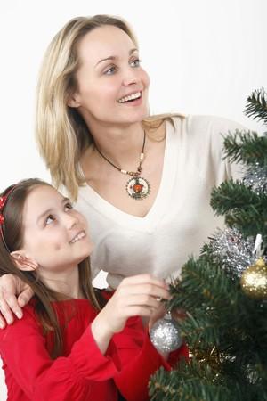 Woman and girl decorating Christmas tree together Stock Photo - 4111129