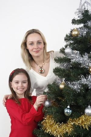 Woman and girl decorating Christmas tree together photo