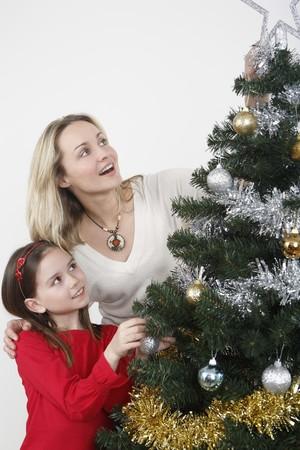 Woman and girl decorating Christmas tree together Stock Photo - 4111197